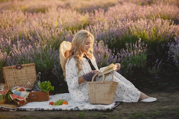 Provence vrouw ontspannen in lavendel veld. dame in een picknick. vrouw met een strohoed.