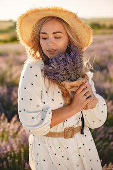 Provence vrouw ontspannen in lavendel veld. dame in een witte jurk. meisje met bloemenboeket.