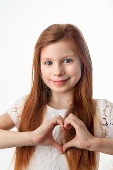 Prtrait van glimlachend vrolijk meisje dat hartvorm met handen op witte achtergrond maakt.