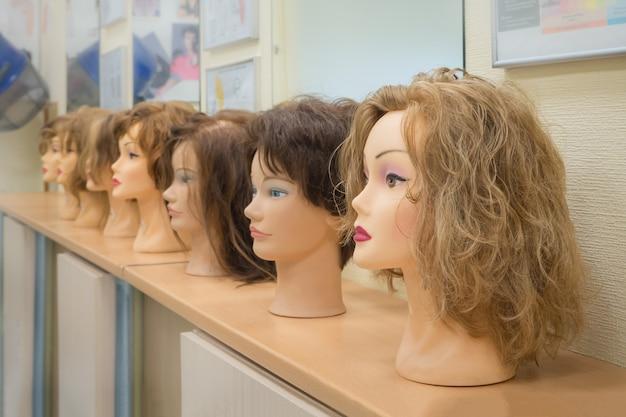 Pruiken op de hoofden van mannequins. schoonheid concept.