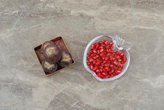 Pruimen in een doosje versierd met glitter en granaatappelpitjes.