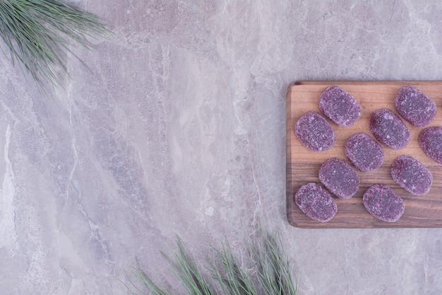 Pruimen marmelades op houten schotel op marmer.