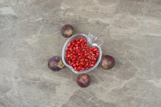 Pruimen met glitter en granaatappelpitjes op marmer.
