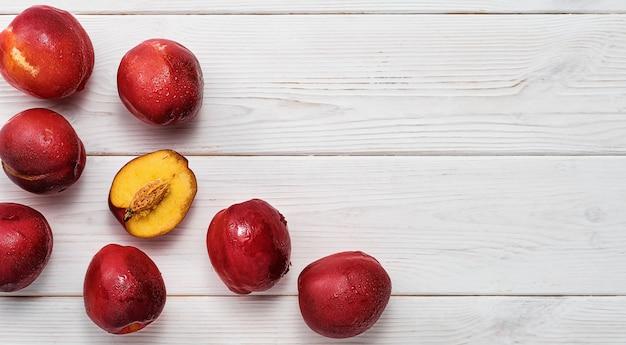 Pruimen op een witte rustieke tafel, lay-out met kopieerruimte. bovenaanzicht van rijpe pruimen met ruimte voor tekst. idee voor ingrediënten voor fruitwijn of taartjam. landbouw, tuinieren, oogstconcept.