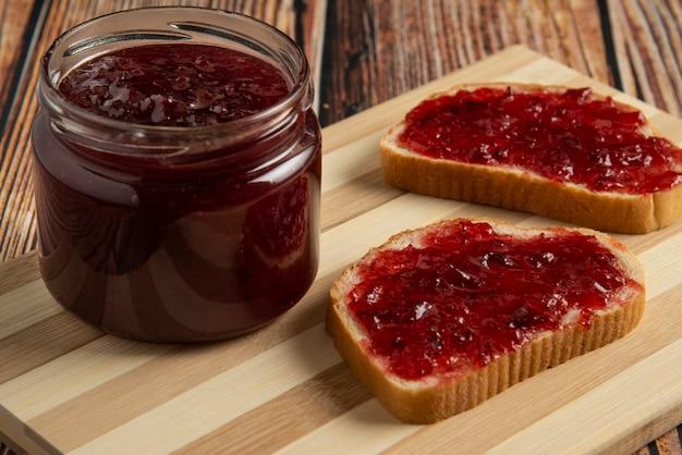Pruimenconfituur in de glazen pot en op de toast.