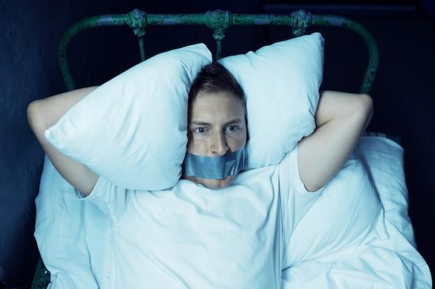 Psycho man met afgeplakte mond liggend in bed, slapeloosheid, donkere kamer ... psychedelische persoon die elke nacht problemen heeft, depressie en stress, verdriet, psychiatrie ziekenhuis