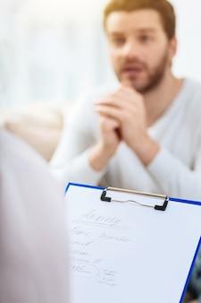 Psychologen merken op. close-up van voorlopige diagnose geschreven door een professionele psycholoog tijdens de fysiologische sessie met een mannelijke patiënt