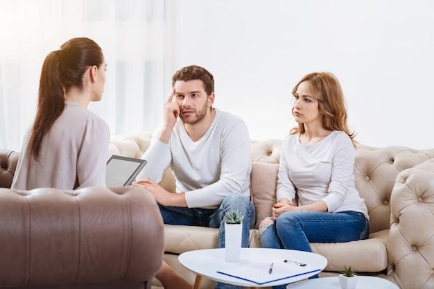 Psychologisch advies. triest ongelukkig jong koppel kijken naar de psycholoog en luisteren naar haar zittend op de bank