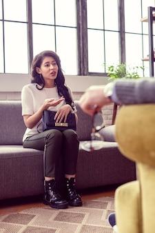 Psychologische consultatie. leuke jonge vrouw zittend op de bank terwijl ze over haar probleem vertelde aan de therapeut