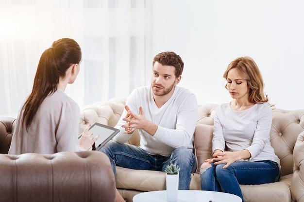 Psychologische sessie. knappe ongelukkig bebaarde man zit met zijn vrouw op de bank en kijkt naar de psycholoog terwijl ze hun probleem aan haar uitleggen