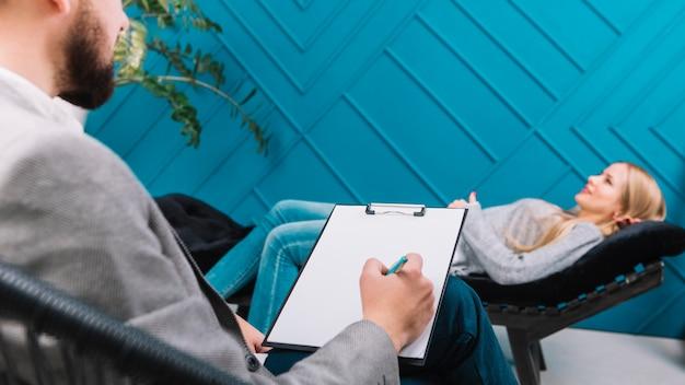 Psycholoog die aan haar vrouwelijke patiënt luistert die op laag ligt en nota's neerschrijft