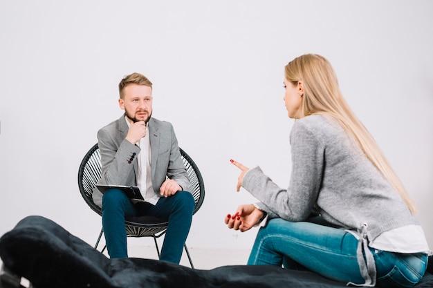 Psycholoog die aan zijn vrouwelijke patiënt in de kliniek luistert