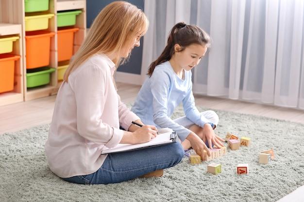 Psycholoog die binnen met een klein meisje werkt