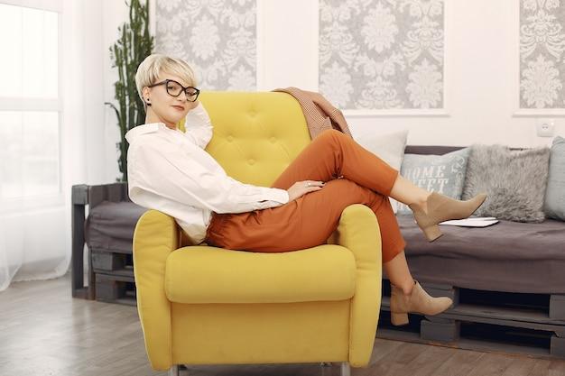 Psycholoog die met glazen op een stoel op het kantoor zit