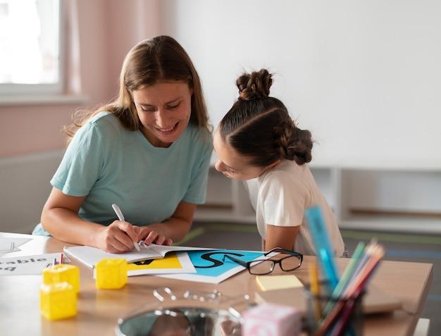Psycholoog helpt een klein meisje bij logopedie