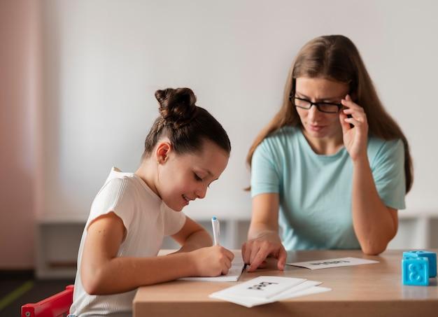 Psycholoog helpt een meisje bij logopedie