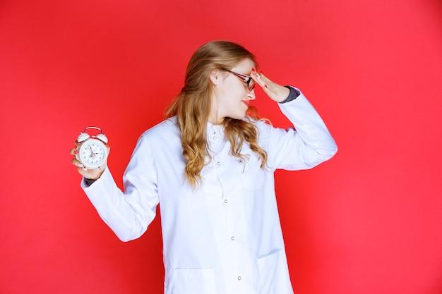 Psycholoog houdt een wekker vast en merkt dat ze laat is.
