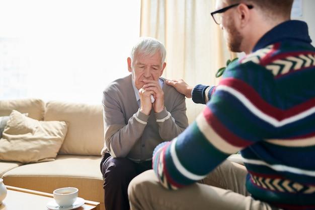 Psycholoog troostend senior man