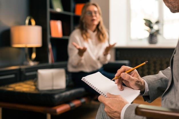 Psychotherapeut luistert naar een vrouwelijke patiënt terwijl hij tijdens de sessie aantekeningen maakt in zijn notitieblok