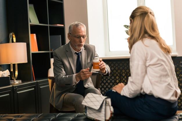 Psychotherapeut zittend in een stoel voor zijn vrouwelijke patiënt terwijl hij een doos met antidepressiva in zijn hand houdt
