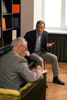 Psychotherapeut zittend in zijn stoel terwijl hij aantekeningen maakt en luistert naar zijn bezorgde patiënt
