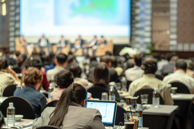 Publiek luisteren luidsprekers op het podium in de conferentiezaal of seminarvergadering