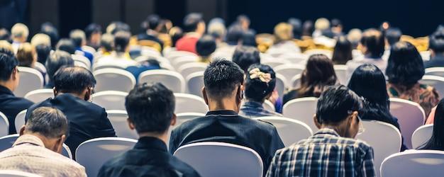 Publiek luisteren sprekers op het podium in de conferentiezaal of seminarbijeenkomst