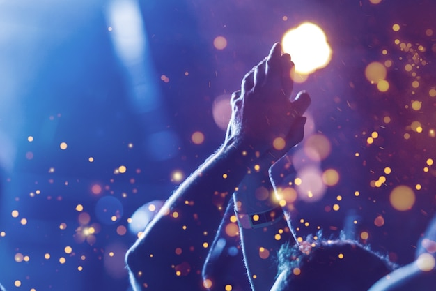 Publiek met opgeheven handen op een muziekfestival en lichten die van boven het podium naar beneden stromen.