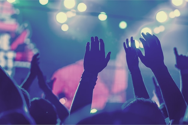 Publiek met opgeheven handen op een muziekfestival en lichtstreaming