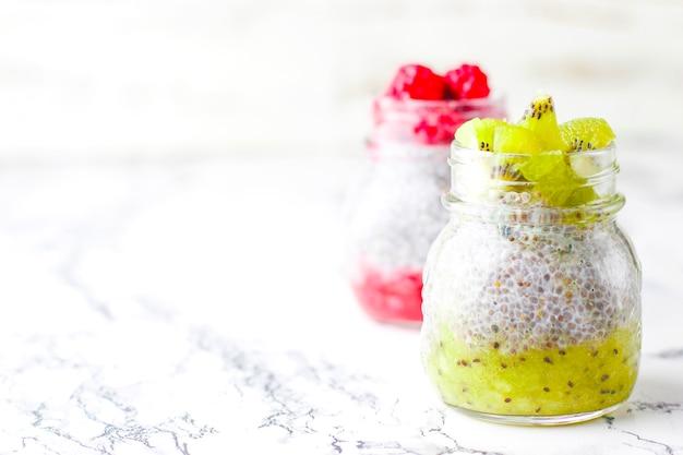 Pudding met bessen, frambozensaus, kiwisaus, bevroren frambozen en bramen en plakjes kiwi