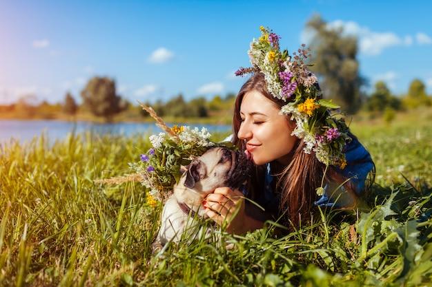 Pug hond en zijn hoofdkoeling door de zomerrivier die bloemkransen dragen