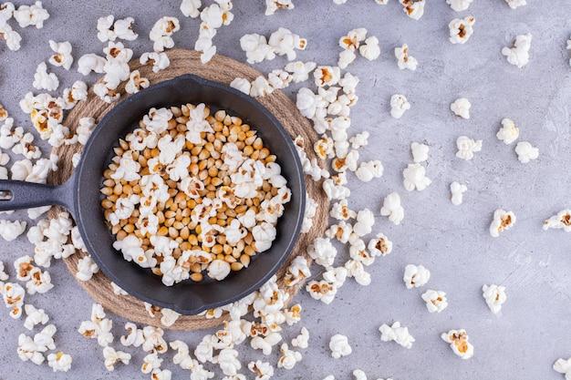 Puinhoop van verspreide popcorn met een pan vol pit in het midden op marmeren achtergrond. hoge kwaliteit foto
