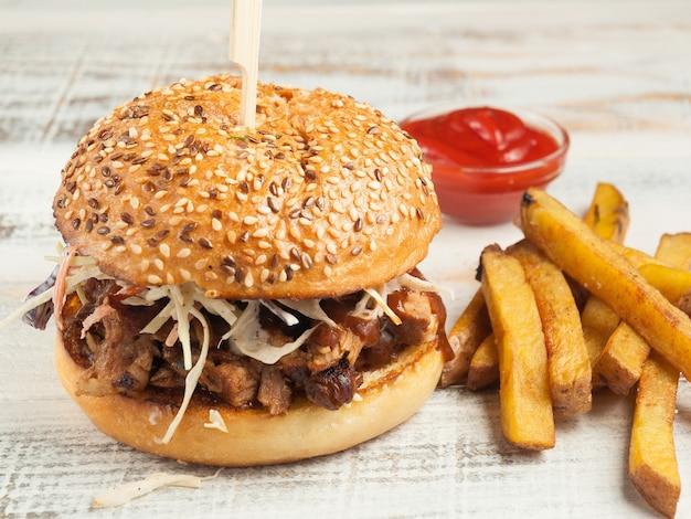 Pulled pork hamburger met frietjes en tomatensaus op een lichte houten tafel