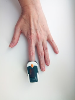 Pulsoximeter aan een vinger bij een volwassen vrouw, meting van het zuurstofniveau in het bloed