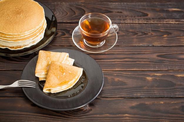 Puncakes met honing en kopje thee op oude houten oppervlak