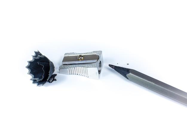 Puntenslijper en een gebroken potlood. spaanders en een grafiet op witte achtergrond. close-up foto.