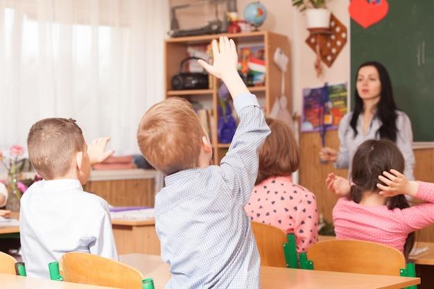 Pupilboys staken zijn hand op in de klas en willen vragen beantwoorden