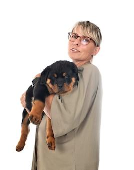 Puppy rottweiler en vrouw voor witte achtergrond