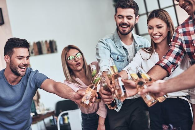 Pure blijdschap. groep jongeren in vrijetijdskleding die elkaar roosteren en glimlachen