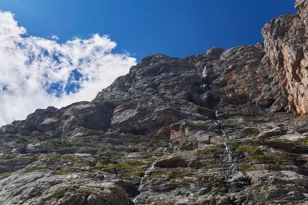Pure klif met een kleine waterval tegen de lucht