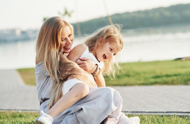Pure liefde. foto van jonge moeder en haar dochter die goede tijd hebben op het groene gras met meer bij achtergrond.
