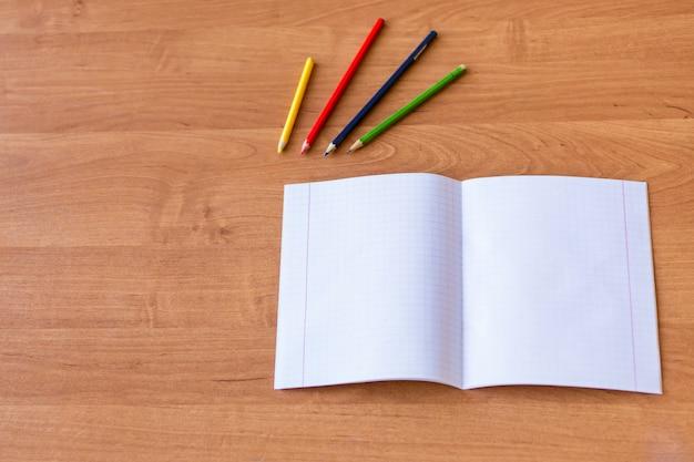 Pure noteboks en kleurrijke potloden op het houten bureau. concept van schoolonderwijs