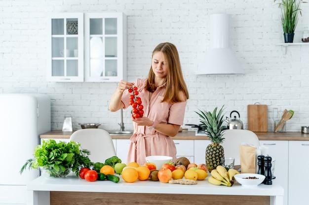 Pure, rijpe sappige tomaten in de handen van de vrouw van een keukenachtergrond