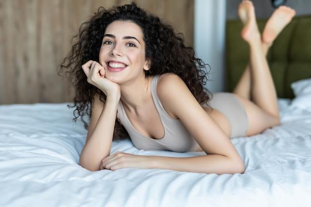 Pure schoonheid. mooie jonge vrouw liggend op het bed thuis