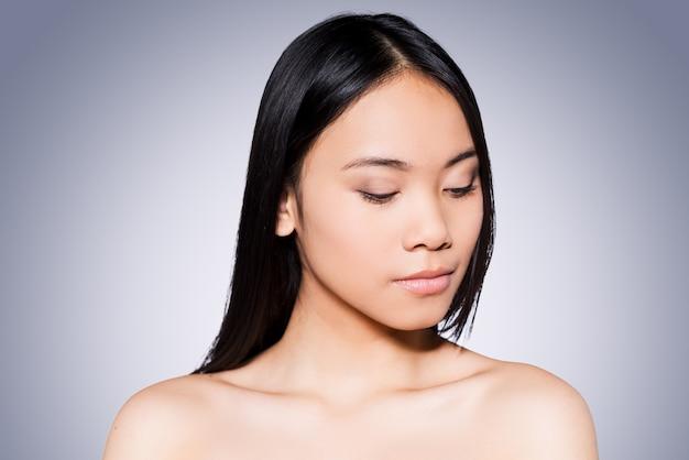 Pure schoonheid. portret van een mooie jonge en shirtloze aziatische vrouw die naar beneden kijkt terwijl ze tegen een grijze achtergrond staat