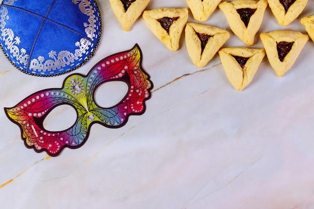 Purim achtergrond met masker, kippa en koekjes.