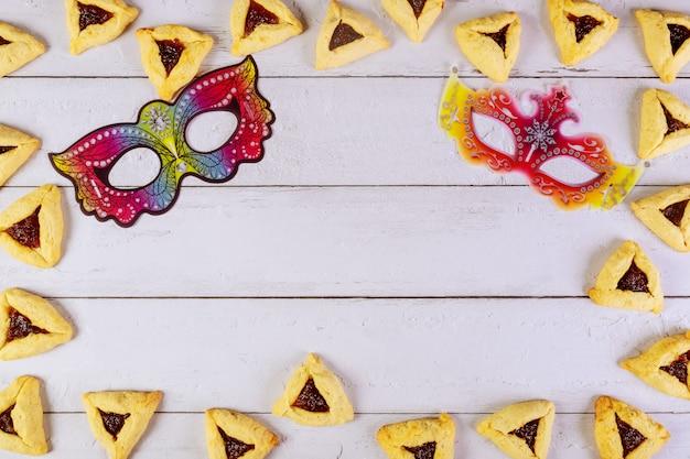 Purim achtergrond met maskers en hamantaschen cookies.