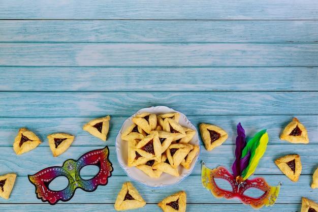 Purim-masker en driehoekskoekjes op wit