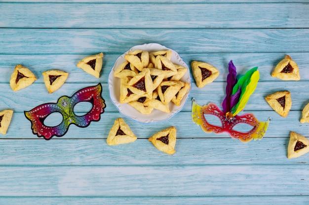 Purim-masker en driehoekskoekjes op witte achtergrond.