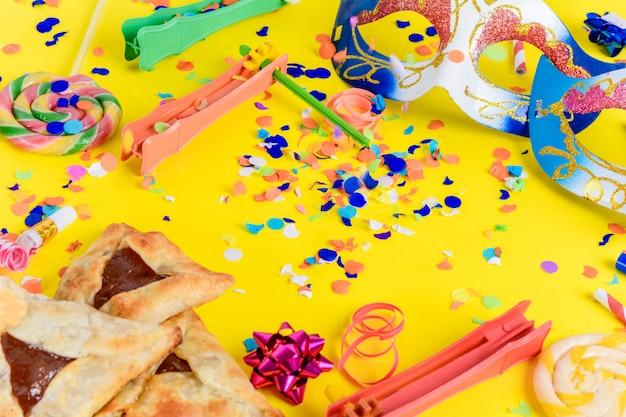 Purim met carnavalsmasker, feestkostuum en hamantasc